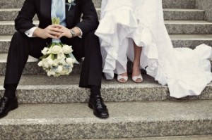 Photo of bride and groom sitting on steps, holding bridal bouquet