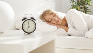 Photo of woman sleeping in bed with alarm clock on nightstand