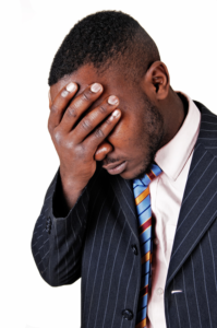 African American Man with hand covering his face feeling nervous