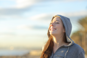 Image of young woman feeling relieved breathing fresh air