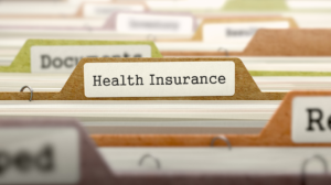 Photo of files with zoom on file labeled health insurance.