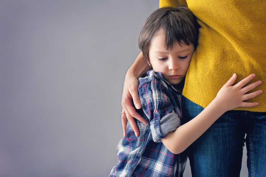 Image of sad child grieving hugging an adult